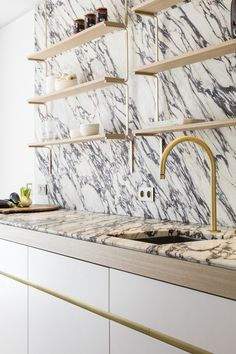 modern kitchen design // gold faucet // open shelving // black and white countertops