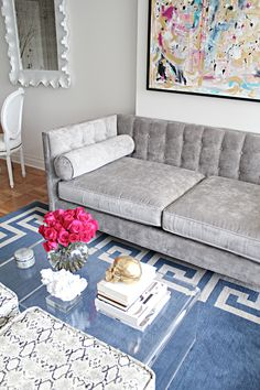 the scalloped mirror and the grey sofa. blue key rug