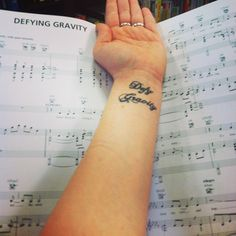 """My tattoo from the Broadway musical """"Wicked"""" In front of the lyrics to the song """"Defying Gravity."""" This tattoo had taught me never to give up my Dreams and hopes for the future just because people tell me I can't. It had taught me that I can do anything if I put my mind to it and that I can Defy Gravity :)"""
