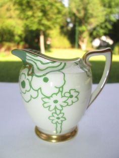 Doulton deco: Glamis creamer, V1312, c1933 (6). Abstract floral design in green with gold gilt highlights and trim.