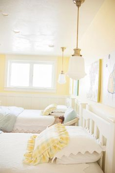 The beautiful color of yellow on the walls in this country-style bedroom is cheery enough for two young girls yet soft enough to grow with them. Pendant lights with individual switches hang above each bed, so the girls can choose to read at night. Light Yellow Bedrooms, Yellow Kids Rooms, Light Yellow Walls, Yellow Girls Bedrooms, Yellow Walls Bedroom, Light Blue, Big Girl Bedrooms, Little Girl Rooms, Home Bedroom