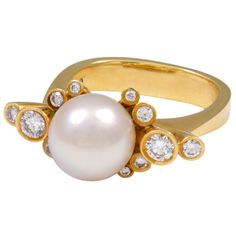 Georg Jensen ring no. 63. 18K gold with 7 mm pearl surrounded by 12 brilliant-cut diamonds.