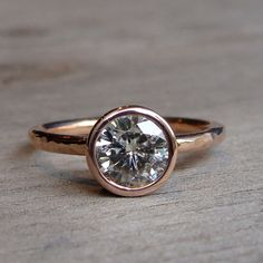 A sparkly and substantial 7mm moissanite (equivalent in size to a 1.25 carat diamond) sits in a handmade tapered bezel on a 2mm round hammered band. All of the metal used in this rings construction is 14k rose gold from recycled sources. The base of the bezel on this ring is notched