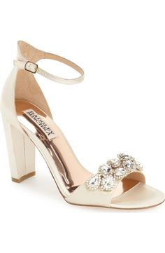Gorgeous crystals dazzle along the toe strap of this elegant evening sandal lifted by a blocky, half-moon heel and topped with an ankle strap.