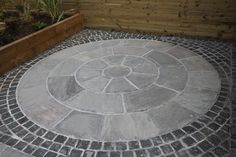 Our Kandla Grey Sandstone Circle has been installed here with Black Granite Setts to define the edge. With matching Kandla Grey paving, step treads, coping and edging all available from stock, this is a very versatile product.