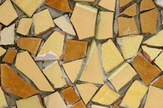 Use grout between broken ceramic tiles on a table top to hold them in place and seal the table.