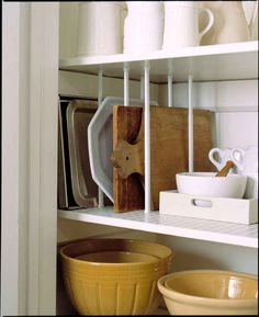 Use tension rods to store your cutting boards and baking sheets so they're easily accessible.