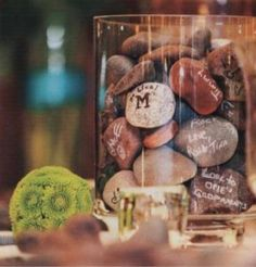 I love this idea. People sign the stones instead of a guest book. The stones are then placed into a glass vase to be used as decoration in the house.