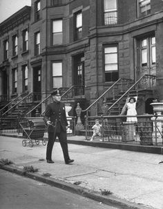 Ed Clark, Children watching a policeman walk his beat in front of apartment buildings, New York City, September 1946.