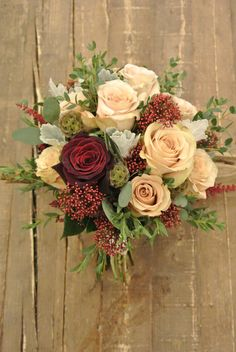 Bridal bouquet with roses, scabiosa pods, skimmia, astilbe, dusty miller and eucalyptus. Antique, loose and beautiful. Designed by Forget-Me-Not Flowers.