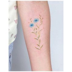 Blue flower tattoo on the left inner forearm. Tattoo artist:...