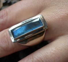 Sterling silver wide ring with a rectangle blue green labradorite stone .