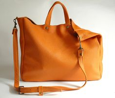 A large minimal bag on shoulder and hand. Made of orange padded leather (2mm). Inside without lining. Dimensions: Height 32 cm (12,6 ), width 38 cm (15), depth about 11 cm (4,3), strap detach, length approximately of 130 cm (51). Fits A4 and more. Close with two magnetic snaps, detal accessories in the color of old gold. For these bag, please expect 1 week for your item to be made and prepared for shipment!  Standard delivery time:  European union: 4 - 10 days  Europe (not EU): 7 - 14 days…