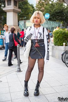 Narumi on the street in Harajuku wearing a Nakid x G.V.G.V. top, UNIF leather skirt, and patent Dr. Martens boots.