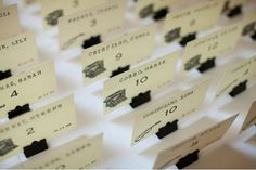 """Wedding seating cards made by rubber stamping in typewriter font on the backs of old library card catalog cards.  The stands are black binder clips from Office Depot with the handles removed.  Wedding """"Due date"""" in the bottom right corner, and a picture to code for meal type in the bottom left corner.  People loved these so much that many took them home as souvenirs!"""