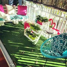 Small balcony with fake grass, colorful furnishings and accessories