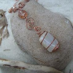 This 17 inch copper wire necklace has been created by wire wrapping a tumble-stone moonstone pendant with copper wire & then shaping the wire to form the necklace. Glass beads have also been incorporated. Watching the rippling reflection of the moon in a puddle inspired this piece. Moonstone has been around for many centuries with the Romans & Greeks both associating it with their lunar goddesses. It is believed by many to bring good fortune to its wearer. It is one of the birthstones for…