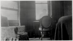 Phantom effect - an unknown man sitting at a desk. Date and photographer unknown.