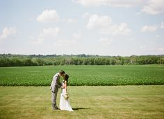 bride and groom kissing with fields and open country in background at Mayowood Stone Barn wedding in Rochester MN | Photo: Laura Ivanova Photography