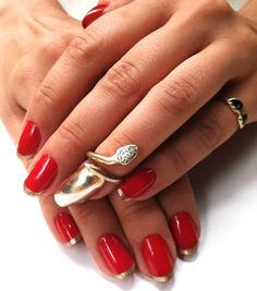 bright red manicure with gold french tips and one gold foil nail (also cute snake ring)
