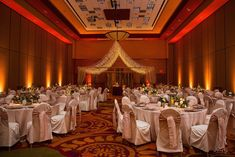 Beautiful blush pink wedding decorations.  White chair covers with elegant blush silk dupioni chair sashes.  Amber gold uplighting at Embassy Suites, East Peoria, IL with lighted canopy over the dance floor.  Taupe jacquard tablecloths complete the elegant and romantic wedding decor.