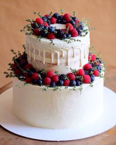 Внутри этого свадебного торта легкие шифоновые бисквиты с натуральной ванилью, ягодная прослойка и сырно-сливочный крем (нижний ярус), а также легкие ванильные бисквиты с кокосовым кремом и кокосовой стружкой и со слоем орехового кранча на молочном шоколаде (верхний ярус). Украшен малиной, ежевикой, голубикой, а также веточками тимьяна. Автор Instagram.com/garnet_bakery