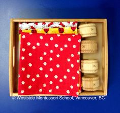 Montessori Practical Life activity - rolling a napkin. The environment and the materials must be appealing to the child. The children just love the fabric on the handmade napkins! The napkins rings are wood finished with beeswax, smooth to the touch. From: @Westside Montessori School (WMS)
