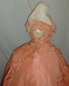 A glorious 1860's three piece pink silk ball gown/dress that has been de-accessioned from the Metropolitan Museum of Art.  The ensemble consists of an evening bodice, over skirt and long trained underskirt.  The dress also comes with a belt that has a center back bow attachment. The fabric has a changeable quality depending on the light reflection.  The bodice has round neckline and short puffed sleeve.  The bodice is decorated with pink silk ruffles that are fringed along the edge.  It is…