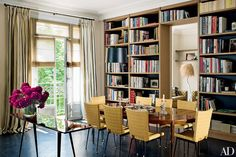 In the Paris dining room of Christian Dior VIP director Mathilde Favier-Meyer, vintage chairs surround a 1940s mahogany table found at Drouot, the French auction house; the bookshelves are oak | archdigest.com