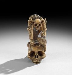 "Japanese Carved Ivory Okimono, Meiji period (1868-1912), the skeleton with two toads and a monkey atop a skull and lotus leaf, unsigned h. 2-3/4""."