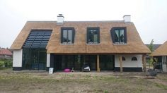 De combinatie tussen landelijk en modern is goed in balans. Wit landhuis met rieten dak. Alle kleuren zijn in balans.: