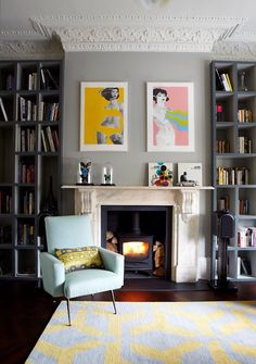 Love the greys, the bookshelves and the fireplace and stove. Funky art for some pops of colour.