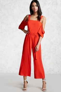A crepe jumpsuit featuring an open-shoulder design, flared short sleeves, a wide-leg, belted waist, and concealed back zipper with a hook-and-eye closure.