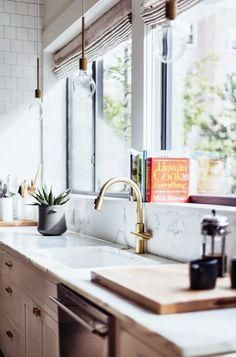Love the marble backsplash behind the sink, brass fixtures and industrial bare bulb pendant lights hanging above! Such a pretty mix!