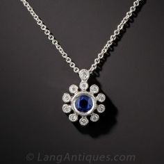Sweet and petite, newly made in bright 18K white gold, a small royal blue collet-set sapphire glistens in the center of 11 small sparkling collet-set diamonds. 3/8 inch diameter, 16 inch chain.