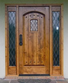 Wood, curved top, leaded glass, clavos (rustic nails). Everything I want in a Tudor door.