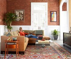 Relaxing and Rustic. With its rich color and texture, exposed brick is a sure way to warm up a room. Here, white trim and a neutral adjacent wall and sofa allow the handsome stone to take center stage. Balance the rustic energy of the walls with something in the center that holds its own, like this vibrant patterned area rug.
