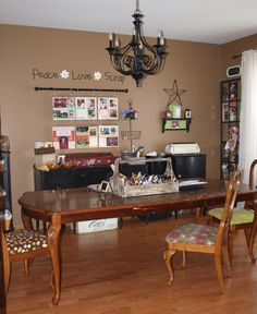 This is my craft room. Actually, was a dining room, and a craft room for the past 7 years.  I get a lot more use of it now!  I took down the light and painted it black last year. Love it now! I recovered all chairs and each has it's own unique fabric (fitting for a craft room I thought). The table was our dining room table. It looks nice, but it was a cheap one.  It's a craft table now for me and my children. It's covered with paint but a table cloth still works if I want a dining room again...