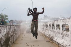 Joseph Duo, a Liberian militia commander loyal to the government, exults after firing a rocket-propelled grenade at rebel forces at a key strategic bridge July 20, 2003 in Monrovia, Liberia. Government forces succeeded in forcing back rebel forces in fierce fighting on the edge of Monrovia's city center. (Photo by Chris Hondros/Getty Images)