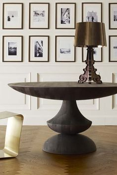 An atypical vignette that reveals a curvaceous table and gold tone bench in front of a gallery of black and white art. A singular lamp sits atop....V