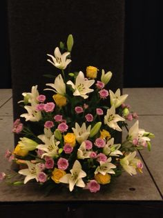 The bouquet in front of the podium are lilies, roses and spray roses.