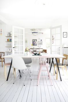 Bright and nordic dining room with white floors and colorfull dining furniture, accessories and artworks.