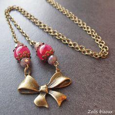 """Collier Petit noeud roseCette série de bijoux fantaisie bronze """"Petit noeud"""" présente des colliers et boucles assorties déclinés autour d'un joli noeud en métal bronze...  Ici, un collier avec des perles en agate fushia & cristal."""