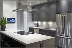 Modiani Kitchens: This kitchen has two hues of grey and white blended together. The cabinets are in grey colour under which the white led lighting is doing its magic.