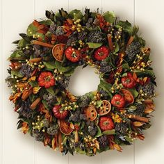 """Quince & Cinnamon Stick Wreath #WilliamsSonoma The rich bounty includes air-dried quince slices and cherry peppers mingled with green salal and myrtle leaves, purple oregano and yellow flax pods. Bundles of cinnamon sticks add a warm accent. Protect from weather. For decorative purposes only. 18"""" diam. $89.95"""