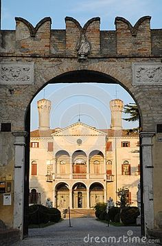 Photo made at Villa Giustinian, also called Castle Roncade for its walls and towers, the villa is a rare example of a noble settlement of '500 and located in the province of Treviso in the Veneto (Italy). The picture shows the facade of the house, lit by the sun, framed by walls on which is the main entrance. Is the background of the blue sky with white clouds lightweight.