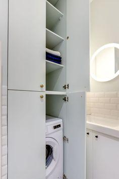 Le coin buanderie s'efface derrière les placards dans cette mini salle de bains