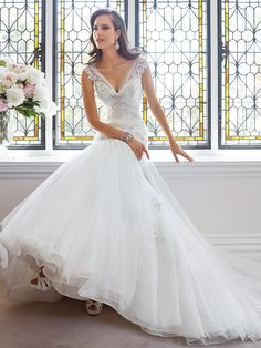 The secret of romance is revealed in Leslie, style Y21442. This beautiful tulle wedding dress with cap sleeves designed by Sophia Tolli.