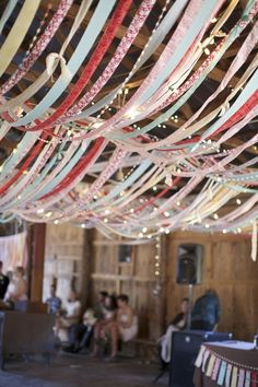 Ribbon or strips of romantic fabric and twinkle light ceiling in a wedding barn or other enclosed area. Instead of summery colors shown here, go for browns, yellows, oranges, and reds for fall. For winter, evergreen, red, or white.