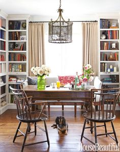 """Floor-to-ceiling bookcases give depth to the dining room — office-library; artfully arranged objects on the shelves engage the eye. """"You need air around things — give them room to breathe,"""" Barrett says. A Danish Baroque desk doubles as a dining table (and a hangout for dachshund Frankie). The mesh lantern from Hollyhock and 19th-century bamboo-turned Windsor chairs add a chinoiserie accent. - HouseBeautiful.com"""